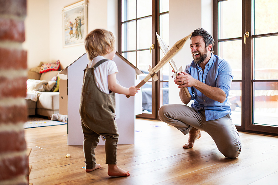 Blog - A Young Boy and Father with Cardboard Swords Playing Indoors at Home