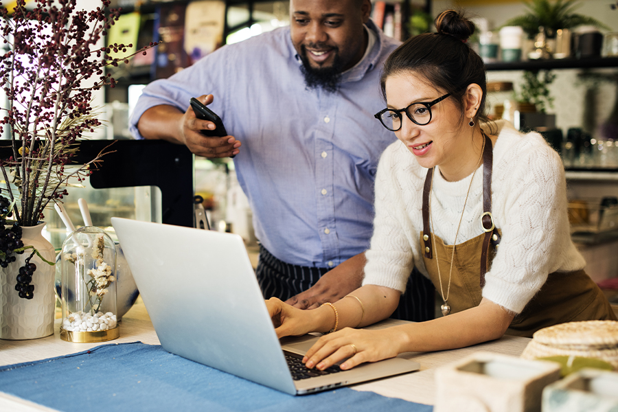 Business Insurance - Business Owner Using Laptop on a Counter With Co-Owner Looking Over Shoulder and Smiling
