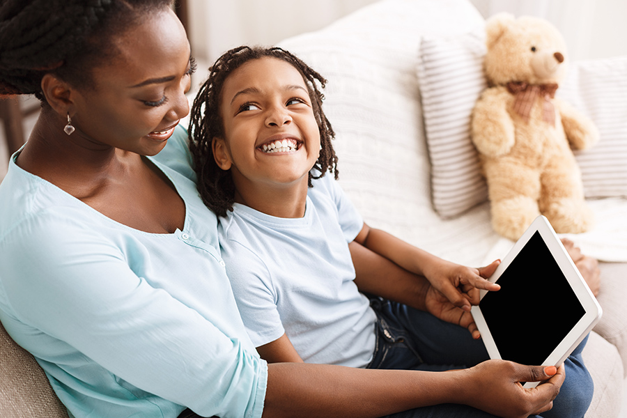 Client Center - Mom Easily Accessing Important Insurance Information While Holding Her Young Daughter and Using a Digital Tablet